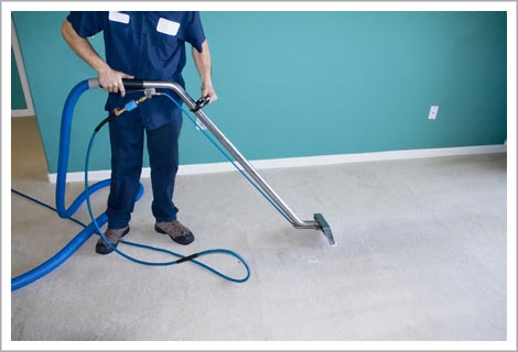 person in blue work cloths using a cleaning device on the floor