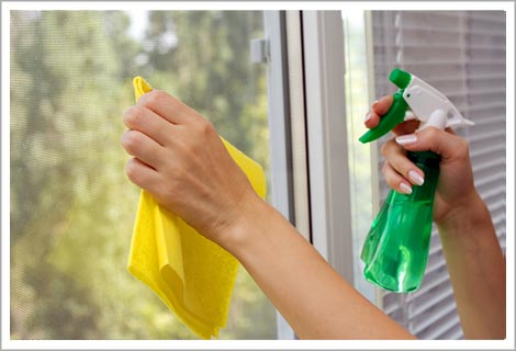 Person cleaning a window with a green spray bottle and yellow rag